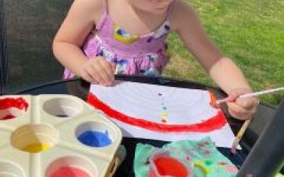 A girl from room 5 enjoys painting outdoors