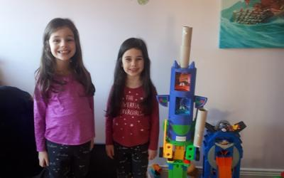 These two sisters were busy building a tower from objects around the house